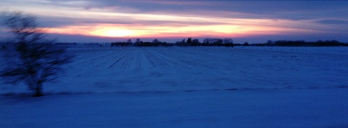 The sun sets on a snowy field whizzing by my car window.